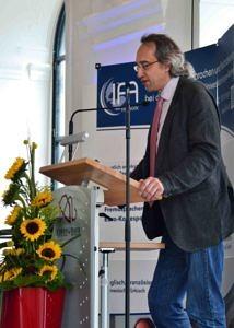 Herr Prof. Dr. Ludwig Fesenmeier, Vorsitzender der Trägervereinigung, steht am Rednerpult und spricht bei der Absolventenfeier im Sommer 2017. Vor dem Rednerpult steht ein Bouquet mit Sonnenblumen.