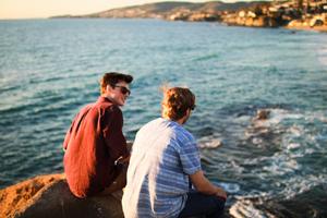 Zwei junge Männer sitzen auf Klippen am Meer und unterhalten sich