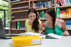 Zwei Studentinnen sitzen an einem Tisch in der Bibliothek vor einem Regal voller Bücher und lernen gemeinsam