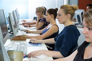 Eine Reihe von Studierenden sitzt vor Bildschirmen und arbeitet konzentriert an den PCs