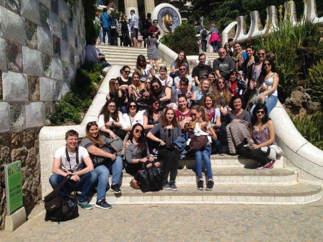 Studierende sitzen im Park Guell für ein Gruppenfoto auf einer Treppe in der Sonne.
