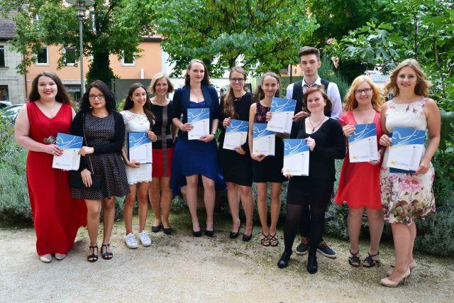 Abgebildet sind Schülerinnen und Schüler mit ihren Europapässen Mobilität 2017, aufgenommen in einem Park nach der Jahresabschlussfeier 2016/2017 in Erlangen.