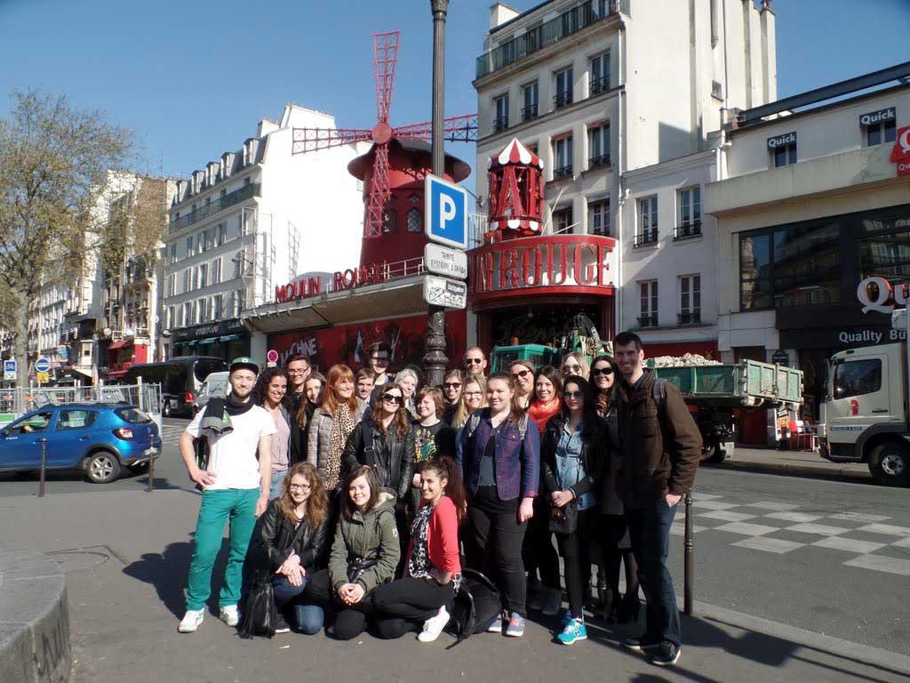 Gruppenbild der Studierenden und Dozenten und Dozentinnen vor dem Moulin Rouge in Paris.