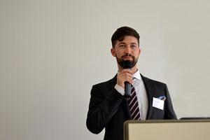 Zu sehen ist der IFA-Absolvent Alexander Podarewski während seines Vortrags beim Career Day 2017 des IFA mit einem Mikrofon in der Hand.
