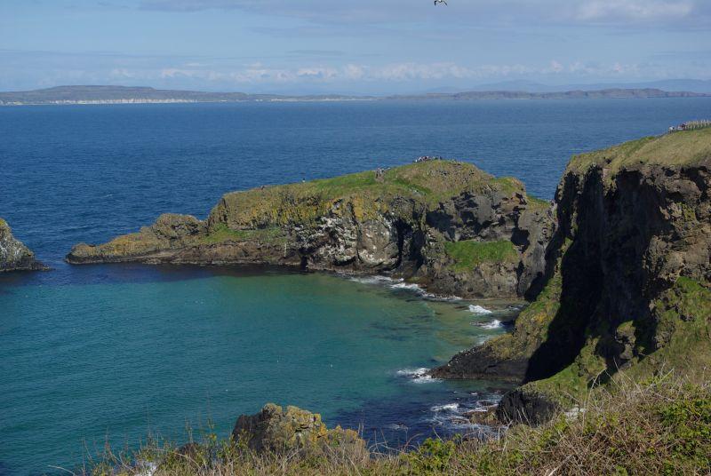 Die Steilküste Irlands in der Sonne mit Blick auf die mit Moos bewachsenen Felsen und das blaue Meer.