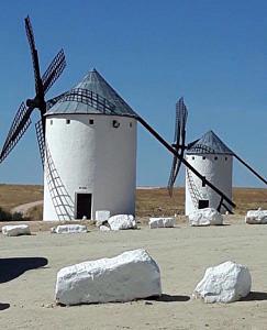 Weiße Windmühlen in Spanien vor blauem Himmel