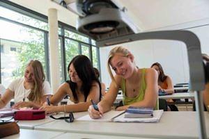 Drei Studentinnen sitzen in der ersten Reihe und schreiben auf Blöcke. Sie lachen und haben Spaß.